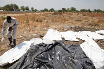 A volunteer in the South Sudanese town of Bor arranges corpses, victims of repeated clashes between government forces and rebels. Photo: Hannah McNeish/IRIN