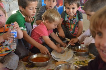 In Khanke village, Iraq Kurdistan Region, children from the Yazidi minority eat a meal of rice and tomato stew for lunch. Photo: UNHCR/N. Colt