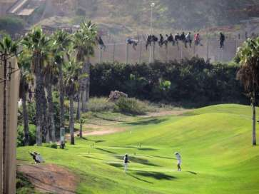 © J. Palazón } Golfers play on a course in Melilla, oblivious to the people crossing the border fence to try and enter the Spanish enclave in North Africa | Source: UNHCR