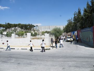 **Children returning home to Aida Palestinian refugee camp north of Bethlehem; Israeli West Bank barrier is in the background. |  Author: Mrbrefast | Wikimedia Commons.