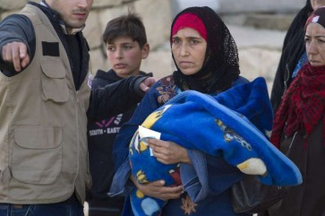 A Syrian refugee mother waits in line with her child to collect aid in Arsal, Lebanon. Photo: UNHCR/M. Hofer