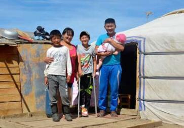 **Photo: ©UNICEF Mongolia/2014/BrownFormer child jockeys Munkh-Erdene (left) and Budgarav (centre) with their parents outside the family ger.