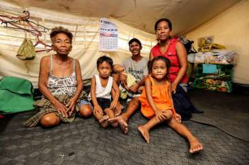 © UNHCR/P.Behan |Three generations of the Aguilar family pose for a photo in their UNHCR tent.