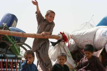 © UNHCR/B.Baloch | Young Afghan refugees on their way home to Afghanistan wave goodbye to Pakistan.