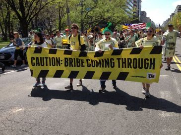 """**Image: """"Caution Bribe Coming Through."""" March in Washington, DC, April 13, 2013, by Represent.Us 