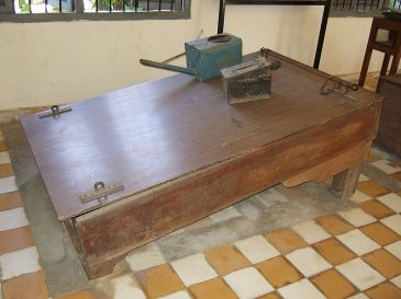 **Image: Waterboard on display at the Tuol Sleng Genocide Museum: prisoners' feet were shackled to the bar on the right, wrists restrained by shackles on the left. Water was poured over the face using the watering can | 7 December 2007 | Source: http://www.flickr.com/photos/waterboardingdotorg/2104419905 | Author: waterboardingdotorg | Wikimedia Commons.