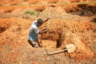 A Kenyan farmer digs a deep hole for a banana tree to thwart erosion. | Source: FAO
