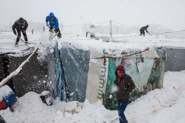 Syrian refugees remove snow from their shelters at an informal tented settlement in the Bekaa Valley, Lebanon, during a blizzard. Photo: UNHCR/A. McConnell