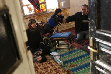 Members of a family gather on the floor of their dilapidated apartment in downtown Amman, Jordan. Photo: UNHCR/B. Szandelszky