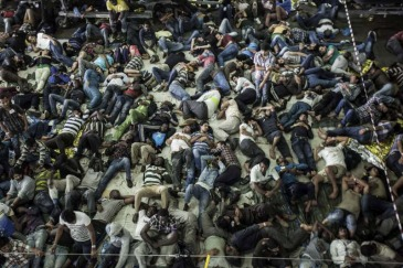 Asylum-seekers and economic migrants take to the seas, waiting out the dangerous journey in the boat's cramped cargo space. Photo: UNHCR/A. D'Amato