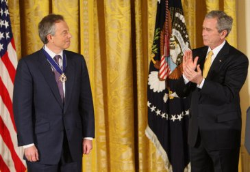 **President George W. Bush applauds former Prime Minister Tony Blair after presenting him Tuesday, Jan. 13, 2009, with the 2009 Presidential Medal of Freedom during ceremonies in the East Room of the White House. | 13 January 2009 | Author: White House photo by Chris Greenberg | Source: whitehouse.gov, President Bush Honors Presidential Medal of Freedom Recipients | Wikimedia Commons