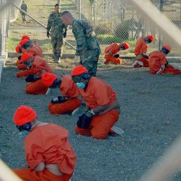 """Detainees in orange jumpsuits sit in a holding area under the watchful eyes of Military Police at Camp X-Ray at Naval Base Guantanamo Bay, Cuba, during in-processing to the temporary detention facility on Jan. 11, 2002. The detainees will be given a basic physical exam by a doctor, to include a chest x-ray and blood samples drawn to assess their health. DoD photo by Petty Officer 1st class Shane T. McCoy, U.S. Navy."""