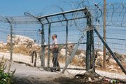 A settler security officer locking a gate in a fence separating Palestinians from their land   UN