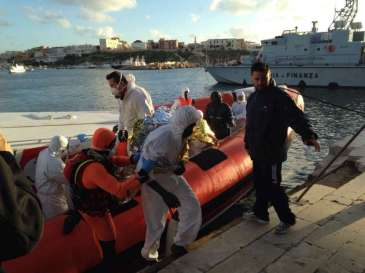 Italian coastguards arrive at the quay in Lampedusa with survivors of this week's tragedy in the Mediterranean. © UNHCR/F.Fossi