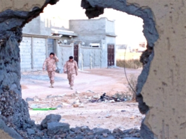 **Photo: Tom Westcott/IRIN | Two soldiers from forces operating under Libya's Tripoli-based government walking through the deserted streets of Bin Jawad.
