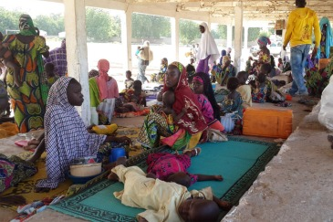 A group of Nigerian refugees rest in the Cameroon town of Mora after fleeing armed Boko Haram attacks. Photo: UNHCR/D. Mbaoirem