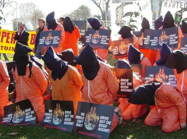 Participants in a rally sponsored by The World Can't Wait are dressed as hooded detainees and holding WCW signs in Upper Senate Park on January 4, 2007. Photo by Ben Schumin. | Sikimedia Commons