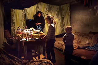 © UNICEF/NYHQ2014-3500/Volpi | Natalia and her little brother, Ivan, stand in the bomb shelter where they and their mother have sought refuge as a result of the ongoing conflict, in the city of Donetsk in Ukraine.