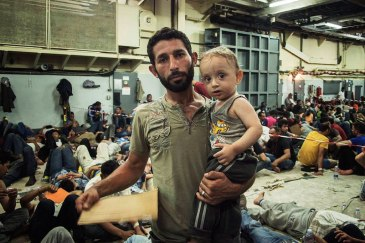 Onboard an Italian ship, a Syrian father holds his one-year-old son as they wait to be checked by doctors. They were rescued in the middle of the Mediterranean. Photo: UNHCR/A. D'Amato