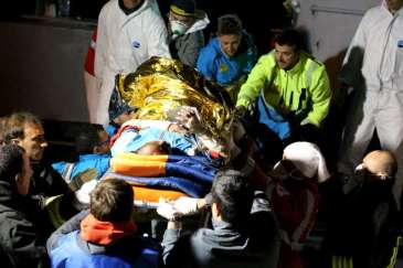 © UNHCR/F. Malavolta | Italian rescue workers rush an injured person, hands swathed in bloodied bandages, off a rescue vessel in Lampedusa.