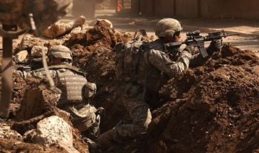 """US Army soldiers in a firefight near Al Doura, Baghdad"""" by Sean A. Foley – [1]. Licensed under Public Domain via Wikimedia Commons"""