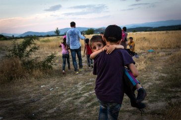A young Syrian refugee carries his brother across the border between Greece and the former Yugoslav Republic of Macedonia (FYROM), near Eidomeni, Greece, in June 2015. Photo: UNHCR/A. McConnell