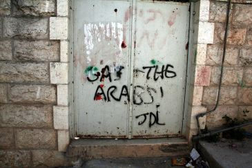 """**Image: """"Gas the Arabs"""" painted on the gate outside a Palestinian home in Hebron by Israeli settlers. It is signed """"JDL"""" (Jewish Defence League)   Author: Magne Hagesæter   Wikimedia Commons"""