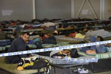 © UNHCR/B. Baloch | Exhausted asylum-seekers after days of walking take some rest at the Rozke police centre before being moved to detention centres elsewhere in Hungary.