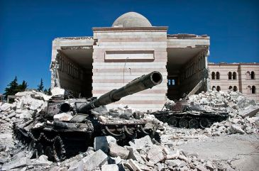 **Two destroyed tanks in front of a mosque in Azaz, Syria. From March 6 to July 23, a battle between the Free Syrian Army (FSA) and the Syrian government was fought for control over the city of Azaz, north of Aleppo, during the Syrian civil war. | Author: Christiaan Triebert | Source: Flickr: Azaz, Syria | Wikimedia Commons