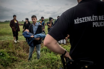 A Syrian refugee shows his ill son to a hungarian police officer and asks for medical help for the kid. | Photo: András D Hajdú | IRIN