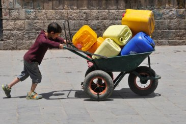 A boy pushes a wheelbarrow filled with jerrycans in Sanaa, the Yemeni, capital. Photo: UNICEF/NYHQ2015-1291/Yasin