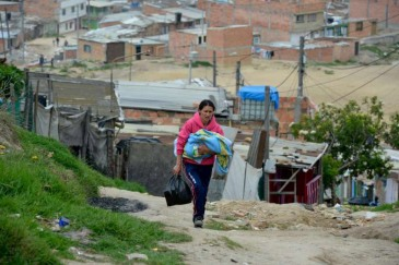 A mother carries her baby through the winding, steep streets of the settlement of Altos de la Florida, Soacha, Colombia. The majority of people in the settlement have been displaced from other areas of Colombia because of fighting and threats by various armed factions. Photo: UNHCR/S. Rich