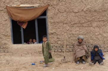 Members of a family sit outside their simple home in northern Afghanistan's Faryab province. Photo: UNHCR/S. Sisomsack