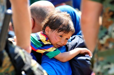 **On 26 August 2015, a distressed child rests over the shoulder of the man carrying him, in the town of Gevgelija, on the border with Greece and the former Yugoslav Republic of Macedonia. Photo: UNICEF/Tomislav Georgiev