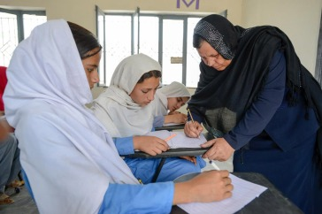 Afghan refugee teacher Aqeela Asifi (right), named as the winner of the United Nations annual Nansen Award. During classes, she pays attention to individual students and monitors their progress. Photo: UNHCR/Sebastian Rich