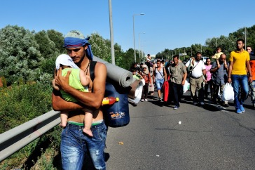Syrian man carrying a baby along the highway with other refugees, several kilometres after leaving Budapest, Hungary, heading in the direction of Vienna, Austria. Photo: UNHCR/Mark Henley
