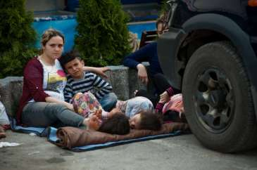 © UNHCR/I.Szabó | Influx of refugees from FYR Macedonia to Serbia includes exhausted mothers with children resting in any kind of shade they can spot.