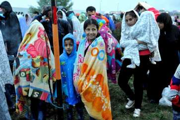 ***Syrian children wearing colorful blankets provided by Austrian volunteers and other refugees at dawn wait patiently for permission to take transport onwards into Austria. © UNHCR/M. Henley