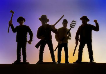 **An artist's depiction of a prototypical angry mob protesting with the threat of violence | Four men, perhaps farmers, make angry gestures while holding an axe, rifle, pitchfork and stick. They typify the traditional Western concept of an angry rural mob protesting something with the threat of violence. | Author: Robert Couse-Baker | Source: Flickr: angry mob | Wikipedia Commons