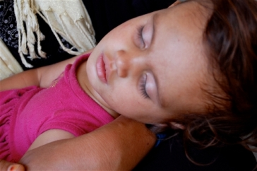 Photo: Chloe Cornish/IRIN | Eighteen month old displaced Iraqi Tabaraq sleeps in her mothers arms
