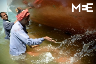 A boat worker splashes water next to the hull of a boat off Masirah Island, Oman MEE/Jerzy Wierzbicki)