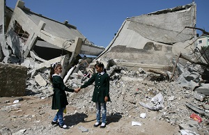 © UNICEF/NYHQ2014-1771/El Baba |  Classmates hold hands while standing beside rubble from a destroyed part of the Shuje'iyah Girls' School in eastern Gaza City.