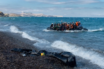 Newly-arriving refugees wave as the large inflatable boat they are in approaches the shore, near the village of Skala Eressos, on the island of Lesbos, in the North Aegean region of Greece. Photo: UNICEF/Ashley Gilbertson VII