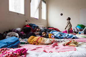 Kiflom watches over his wife, who suffers from headaches and has stopped eating. Conditions here seem to help spread disease. This is one of the few families living here: most residents are single young men.