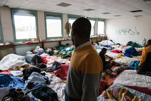 Dozens of people sleep in this classroom. The refugees are grouped by nationality; these are the Sudanese.