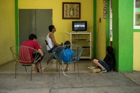 Children watch television at the Buen Pastor shelter in Tapachula