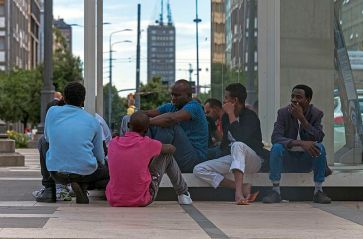 African_men_sitting_on_the_Piazza_duca_d'Aosta,_Milan,_in_evening