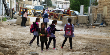 Children heading home from school pass the yellow steel gate at Qafisheh checkpoint in Hebron's Tel Rumeida neighborhood on 2 May 2019. (Photo_ Ivan Karakashian_NRC)