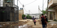 children walk past qafisheh checkpoint on a muddy road on their way home from school in hebron's tel rumeida neighborhood on 2 may 2019. (photo_ ivan karakashian_nrc)