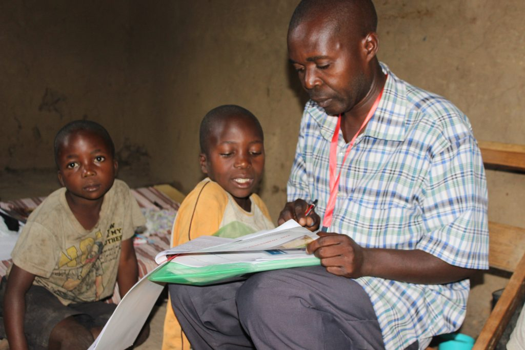 A-parent-helps-his-children-to-go-through-some-of-the-study-kits-recieved-from-ECW-implementing-partners-in-Uganda--1024x683